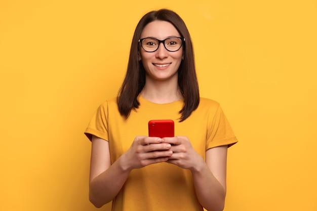 Sorridente giovane donna con capelli castani in occhiali tipi messaggio di testo sullo smartphone