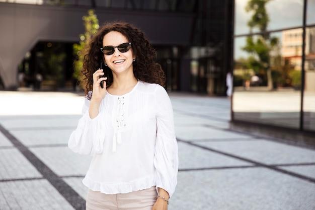 Sorridente giovane donna con i capelli ricci, guardando il telefono cellulare, contro un edificio con sfondo della finestra.