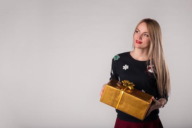 Sorridente giovane donna con scatola regalo