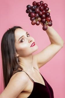 Sorridente giovane donna con uva viola. bella bruna su uno sfondo rosa.