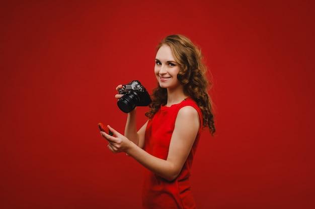 Una giovane donna sorridente con i capelli mossi tiene in mano una fragola e la fotografa, tenendo in mano una deliziosa fragola fresca su uno sfondo rosso brillante.