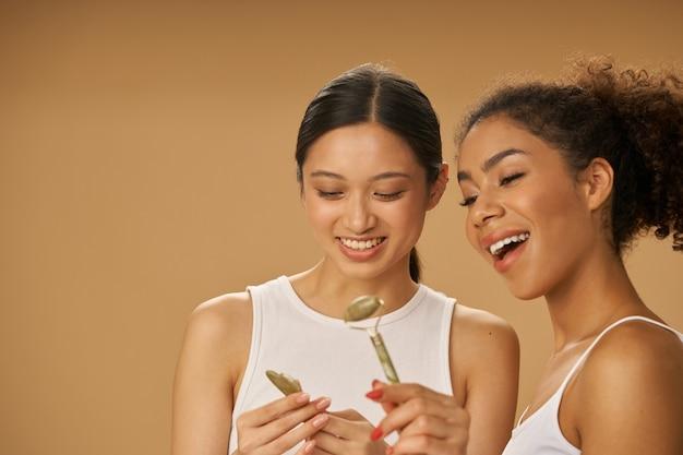 Giovani donne sorridenti che tengono guardando il rullo di giada e il gua sha facciale mentre posano insieme