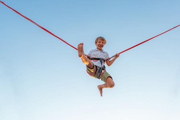 Sorridente ragazzo eccitato che salta su un trampolino con assicurazione.