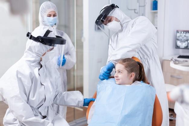 Sorridente bambina nel corso dell'esame dentistico vestita in tuta a causa della pandemia di coronavirus. stomatologo durante il covid19 che indossa una tuta in dpi facendo la procedura dei denti del bambino seduto su ch