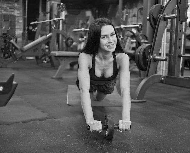 Smilling bruna sport in un abbigliamento sportivo facendo esercizio con rullo abs in palestra e guardando la fotocamera