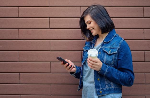 Sorridente giovane donna caucasica bruna in una giacca di jeans blu con lo smartphone in piedi davanti al muro di mattoni che tiene in mano il caffè caldo.