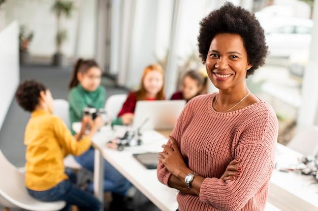 Sorridente insegnante di scienze femminile afro-americana con un gruppo di bambini che programmano giocattoli elettrici