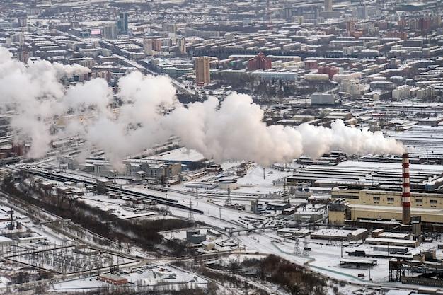 Smog in una città europea, veduta aerea, ambiente povero nella moderna città industriale. fumo denso bianco da alti tubi di fabbrica. vista dall'alto dell'impianto di riscaldamento.