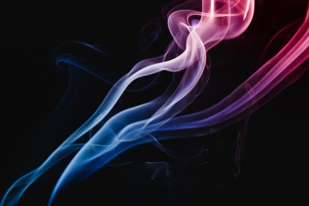 Fumo colorato che fluttua nell'aria su sfondo scuro