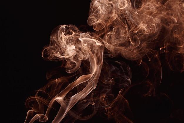Fumo che fluttua nell'aria su sfondo scuro. colore oro rosa