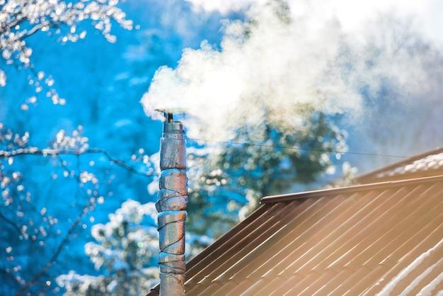 Fumo dal camino sul tetto al giorno pieno di sole