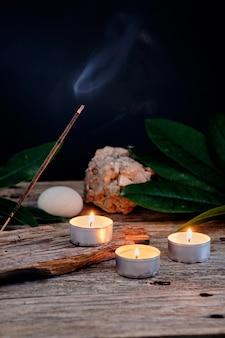 Fumo da bastoncini di incenso e candele rilassanti su legno rustico