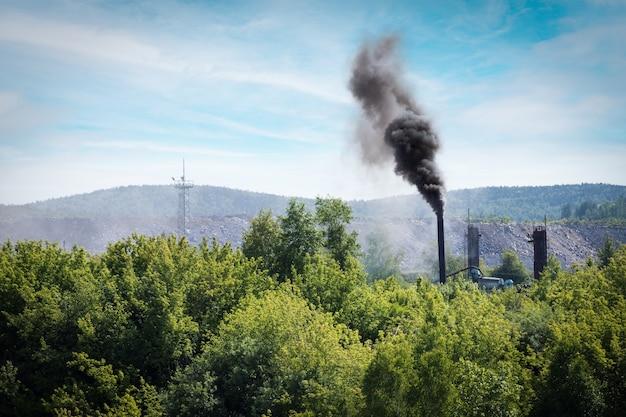 Pennacchio di fumo proveniente dall'industria che emette nell'atmosfera sullo sfondo degli alberi forestali e sul cielo blu. problema ambientale. concetto ecologico.