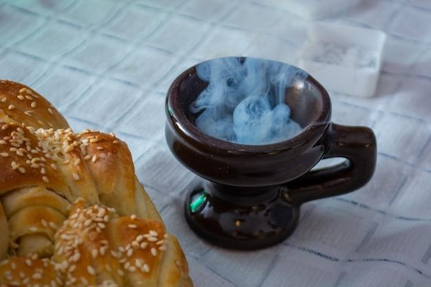 Fumo che sale da cresset sulla tavola con il cibo nella pasqua ortodossa