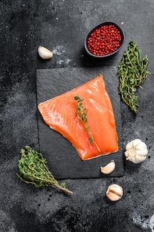Filetto di salmone dell'atlantico affumicato. pesce biologico. sfondo nero. vista dall'alto.