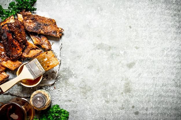 Costolette barbecue affumicate con birra ed erbe aromatiche su uno sfondo di pietra