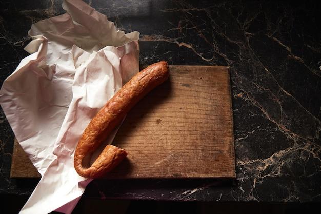 Salsiccia affumicata di manzo o maiale su vecchio tagliere con coltello
