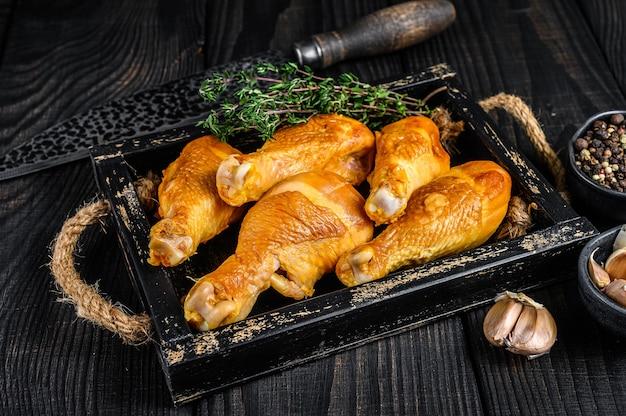 Cosce di coscia di pollo affumicate con erbe e spezie sulla tavola di legno. vista dall'alto.