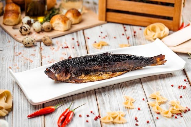 Pesce aringa affumicato su una tavola di legno leggera del piatto