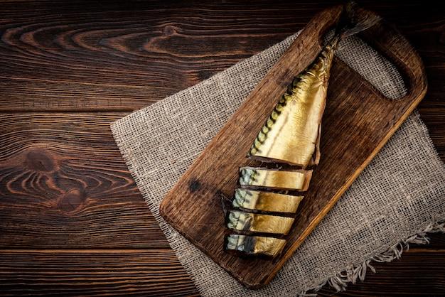 Sgombro affumicato su tavola di legno sul tavolo di legno scuro.