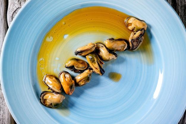 Cozze affumicate sott'olio su piatto in ceramica blu su superficie in legno grigio. vista dall'alto, piatto. avvicinamento