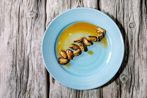 Cozze affumicate sott'olio su piatto di ceramica blu su superficie di legno grigio vecchio. vista dall'alto, piatto. copia spazio