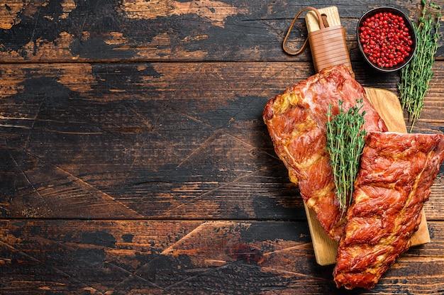 Costine di maiale affumicate con salsa piccante. fondo in legno scuro. vista dall'alto. copia spazio.