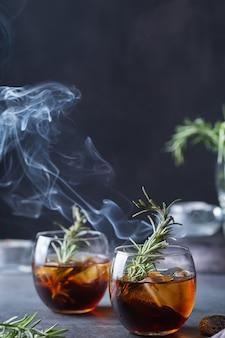 Rosmarino affumicato cocktail vecchio stile su un tavolo