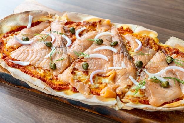 Pizza al salmone affumicato su tavola di legno