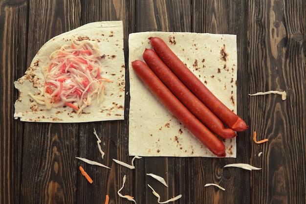 Salsiccia affumicata e cavolo cappuccio su pane pita isolato su sfondo di legno.