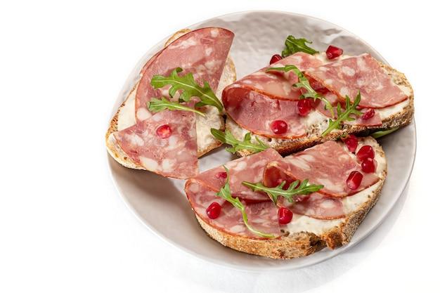 Salsiccia affumicata e panini con crema di formaggio su un piatto. decorato con erbe di aneto. su uno sfondo bianco. isola. copia spazio.