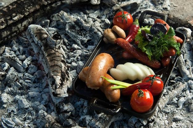Salsicce affumicate e pomodori giacciono su carbone. il piatto è cotto e affumicato alla brace