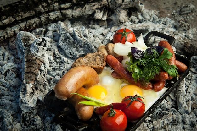 Salsicce affumicate con pomodori e uova giacciono su carbone. il piatto è cotto e affumicato alla brace