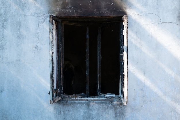 Una finestra affumicata di una casa dopo un incendio.