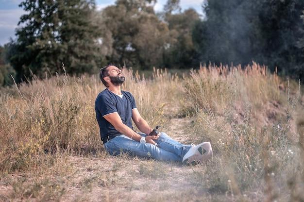 Fumatore che fuma un dispositivo di fumo elettronico sul suolo della foresta