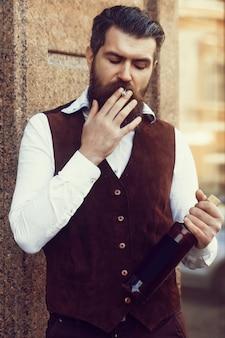 Fumatore con bottiglia di vino che fuma sigaretta