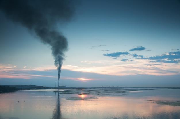 Camini fumanti vicino al lago nel cielo serale.