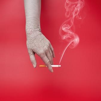 Fumare sigaretta in una mano secca e screpolata, effetti negativi del fumo sulla pelle.