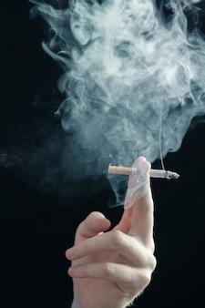 Fumo di sigaretta in mano sulla superficie nera