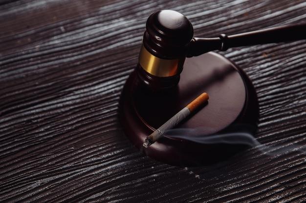 Fumo di sigaretta e primo piano in legno del martelletto del giudice. dipendenza pericolosa