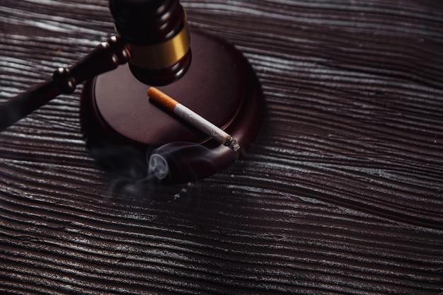 Fumo di sigaretta e martelletto in legno del giudice su un tavolo.