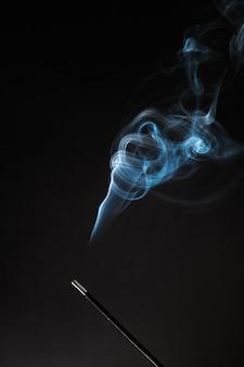Bastoncino di incenso fumante con fumo rilassante che sale.