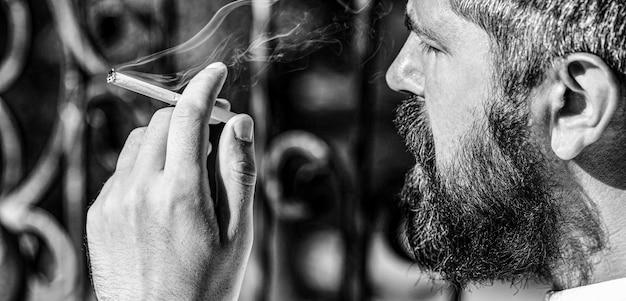 Fumo maschio, fumo di sigaro. uomo di fumo con la barba. uomo giovane hipster fuma.