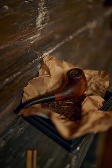 Tubo di fumo e una pila di tabacco su un tavolo di legno, primo piano, nessuno