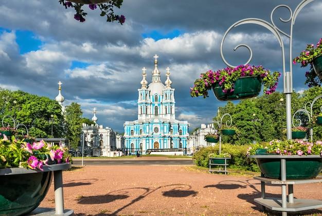 Cattedrale smolny a san pietroburgo, circondata da bellissimi fiori e nuvole scure in una soleggiata giornata estiva