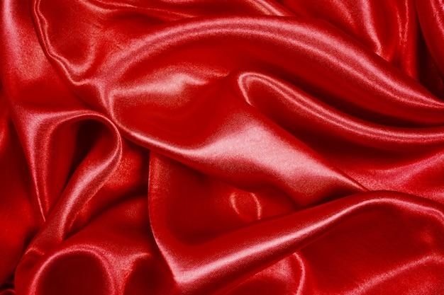 La seta rossa elegante liscia o la struttura del raso possono usare come fondo astratto, tessuto