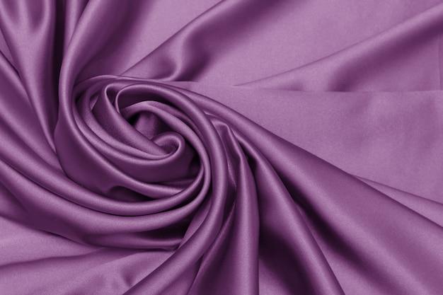 La consistenza elegante e liscia del tessuto di lusso in raso o seta può essere utilizzata come sfondo astratto.