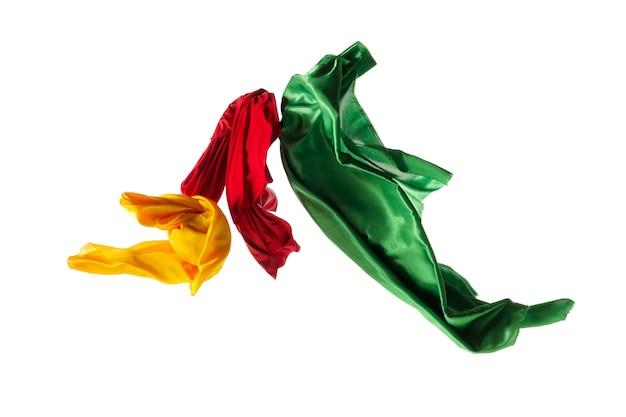 Panno giallo, rosso, verde trasparente elegante liscio separato su fondo bianco.