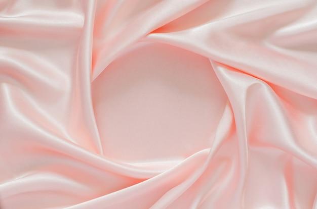 Fondo di struttura del panno di raso rosa ondulato elegante liscio con spazio per il testo