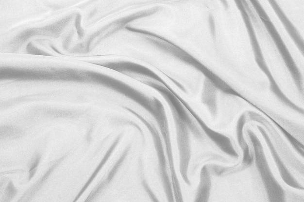 Il tessuto di seta bianco elegante liscio o la trama di un panno di raso di lusso possono essere utilizzati come sfondo del matrimonio
